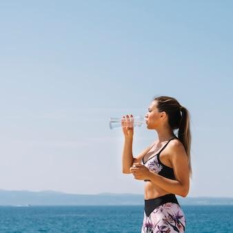 Vista lateral, de, um, mulher jovem, ficar, frente, mar, bebendo, água, de, garrafa