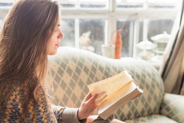 Vista lateral, de, um, mulher jovem, girar página, de, livro