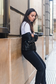 Vista lateral, de, um, mulher jovem, inclinar-se, parede, pela calçada