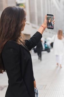 Vista lateral, de, um, mulher jovem, levando, selfie, ligado, smartphone, em, cidade