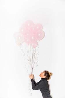 Vista lateral, de, um, mulher jovem, segurando, cor-de-rosa, balões, em, mão, isolado, branco, fundo