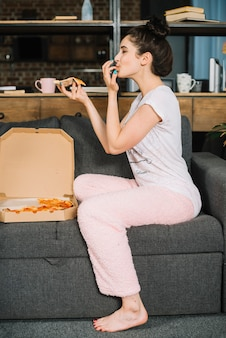Vista lateral, de, um, mulher jovem, sentar sofá, comendo pizza