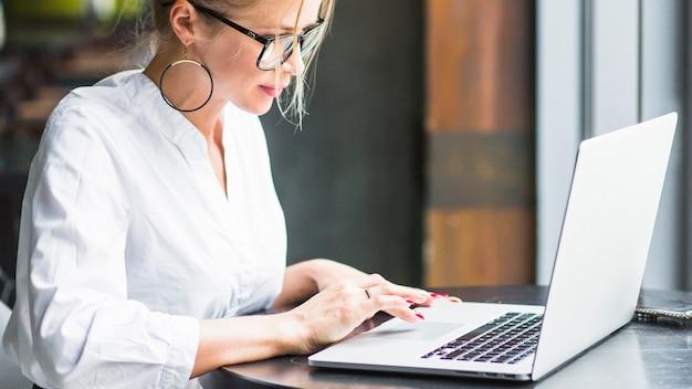 Vista lateral, de, um, mulher, trabalhar, laptop, em, restaurante