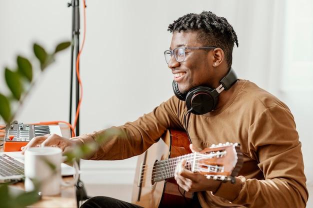 Vista lateral de um músico sorridente em casa tocando violão e mixando com o laptop