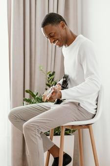 Vista lateral de um músico sorridente tocando guitarra elétrica em casa
