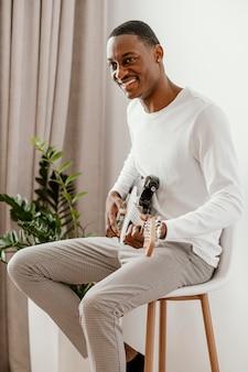 Vista lateral de um músico sorridente tocando guitarra elétrica