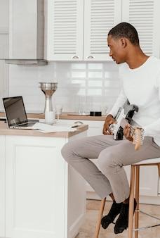Vista lateral de um músico tocando guitarra elétrica e olhando para o laptop