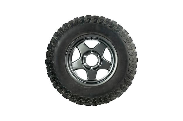 Vista lateral de um pneu todo-o-terreno com roda de liga leve isolada no fundo branco.