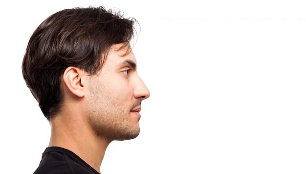 Vista lateral de um retrato facial de jovem bonito isolado no branco