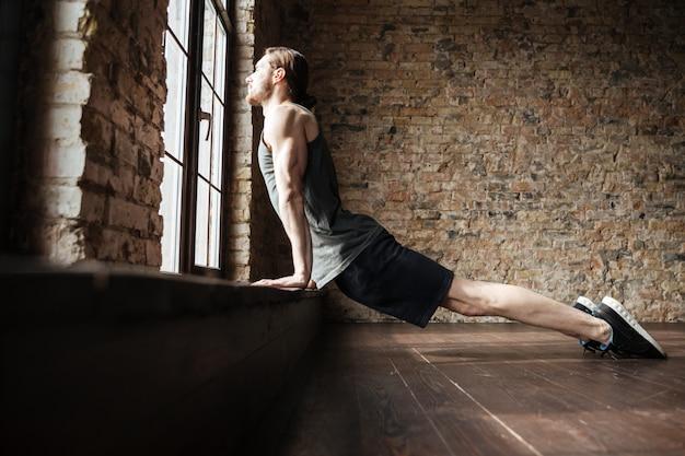 Vista lateral de um sério jovem desportista saudável fazendo exercícios