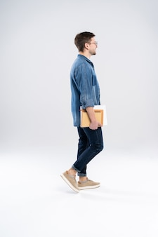 Vista lateral de um sorridente jovem casual caminhando, estudante com notas de ang do livro.
