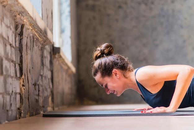 Vista lateral, de, um, sorrindo, mulher jovem, fazendo, pushup, ligado, esteira exercício