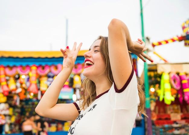 Vista lateral, de, um, sorrindo, mulher jovem, gesticule, sinal paz