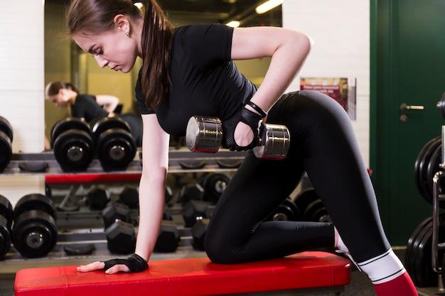 Vista lateral, de, um, sportive, mulher jovem, fazendo, exercício, com, dumbbell