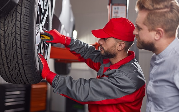 Vista lateral de um técnico de manutenção profissional com uma chave inglesa examinando a roda de um automóvel quebrado de um cliente do sexo masculino na estação de serviço