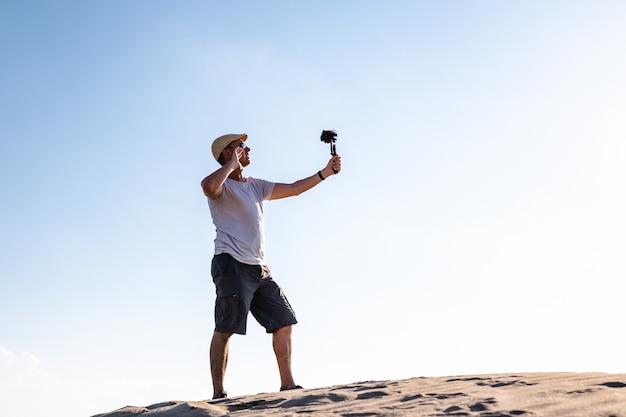 Vista lateral de um viajante masculino em uma duna de areia e filmando conteúdo para mídia social