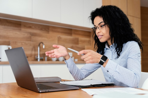 Vista lateral de uma adolescente em casa durante a escola online com laptop