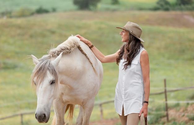 Vista lateral de uma agricultora acariciando seu cavalo
