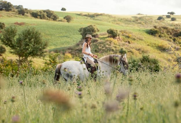 Vista lateral de uma agricultora cavalgando ao ar livre