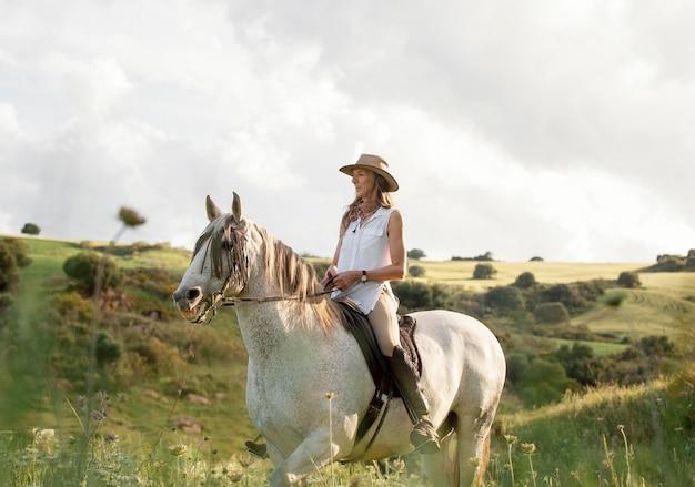 Vista lateral de uma agricultora cavalgando na natureza