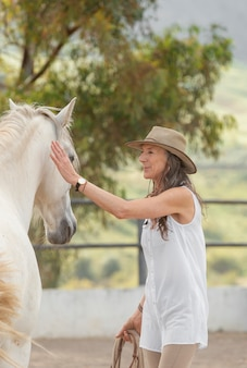 Vista lateral de uma agricultora com seu cavalo no rancho