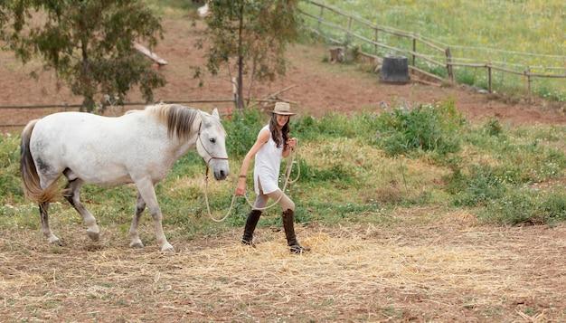 Vista lateral de uma agricultora com seu cavalo