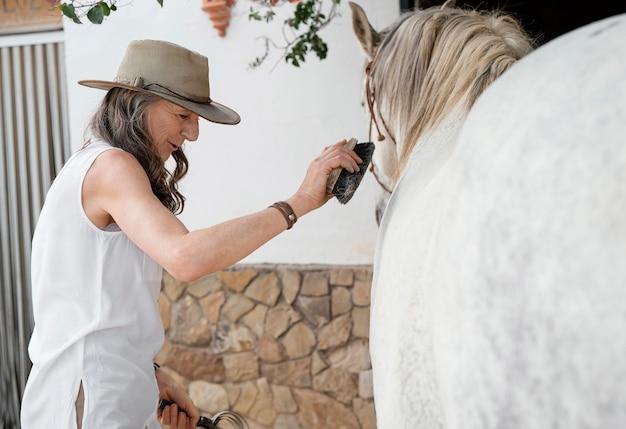 Vista lateral de uma agricultora escovando seu cavalo no rancho