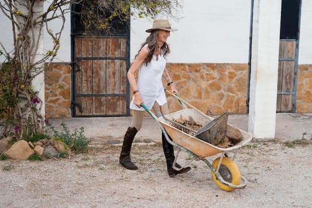 Vista lateral de uma agricultora segurando um carrinho de mão
