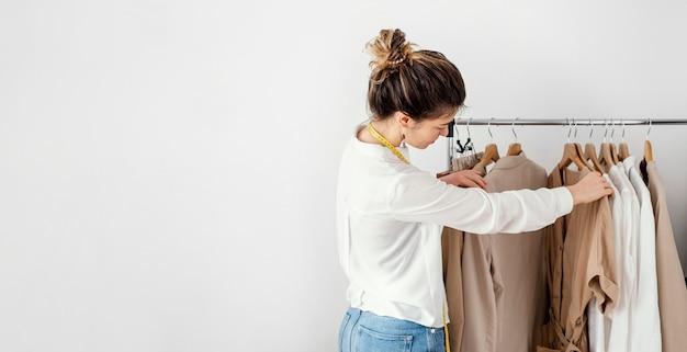 Vista lateral de uma alfaiate olhando as roupas em cabides com espaço de cópia