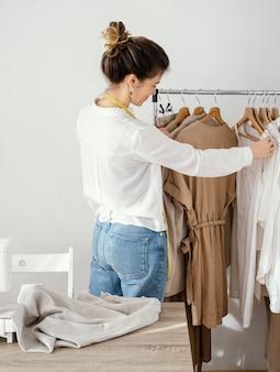 Vista lateral de uma alfaiate olhando as roupas em cabides
