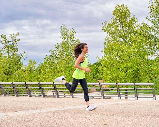 Vista lateral de uma atleta feminina sorrindo enquanto pratica correr no parque. ela é morena e seu cabelo está se movendo