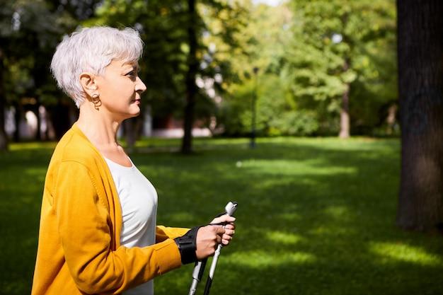 Vista lateral de uma atraente mulher aposentada atlética com corte de cabelo grisalho, apreciando a caminhada nórdica usando varas especiais, fazendo exercícios aeróbicos em bom dia de outono na zona rural. idade e estilo de vida