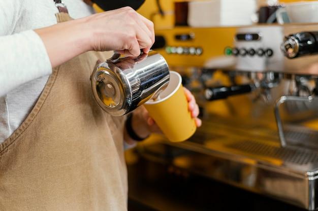 Vista lateral de uma barista com avental servindo leite no copo