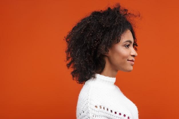 Vista lateral de uma bela jovem africana sorridente, vestindo uma camisola em pé sobre a parede vermelha