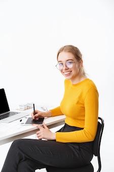 Vista lateral de uma bela jovem designer gráfica sentada no local de trabalho, trabalhando em um laptop de tela em branco e um tablet isolado sobre uma parede branca