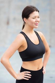 Vista lateral de uma bela mulher em athleisure posando ao ar livre
