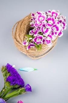 Vista lateral de uma bola de corda com cravo turco de cor roxa e flores de statice na mesa branca