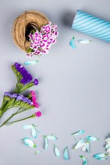 Vista lateral de uma bola de corda com cravo turco de cor roxa e statice flores na mesa branca com espaço de cópia
