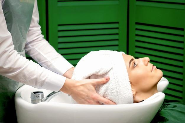 Vista lateral de uma cabeleireira seca o cabelo da cliente com uma toalha na pia de um salão de cabeleireiro