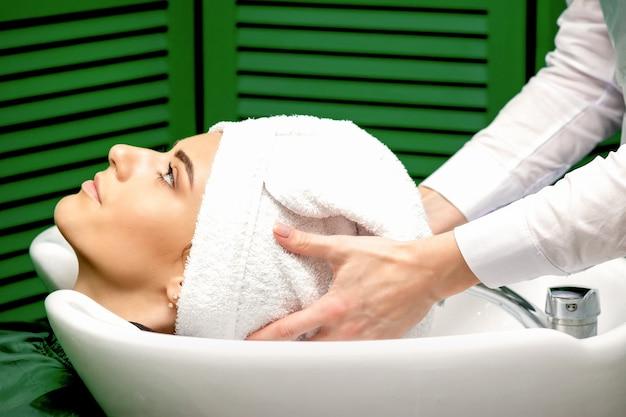 Vista lateral de uma cabeleireira seca o cabelo das clientes com uma toalha na pia de um salão de cabeleireiro