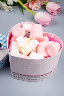Vista lateral de uma caixa de presente em forma de coração cheia de marshmallow e tulipas cor de rosa com flores de alstroemeria na mesa branca