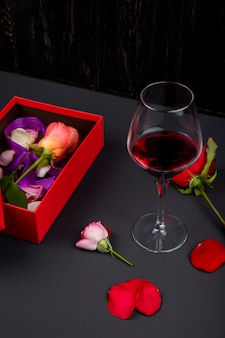 Vista lateral de uma caixa de presente vermelha aberta com flor rosa e um copo de vinho tinto na mesa preta