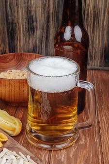 Vista lateral de uma caneca de cerveja com amendoins salgados em uma tigela de madeira no rústico