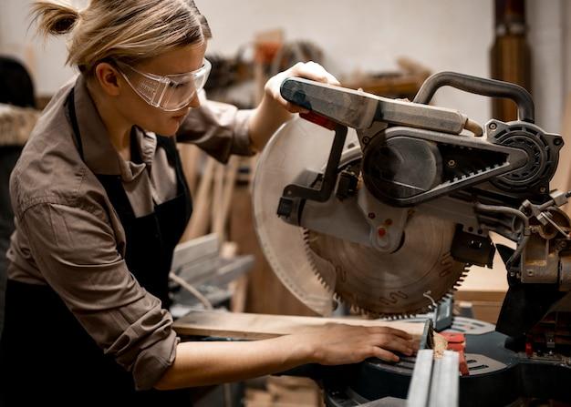 Vista lateral de uma carpinteira com óculos de segurança e ferramenta
