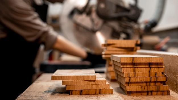 Vista lateral de uma carpinteira no estúdio usando uma serra elétrica