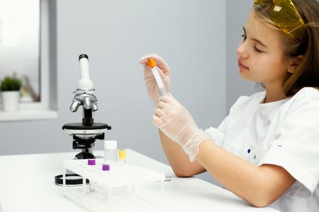 Vista lateral de uma cientista com óculos de segurança e microscópio
