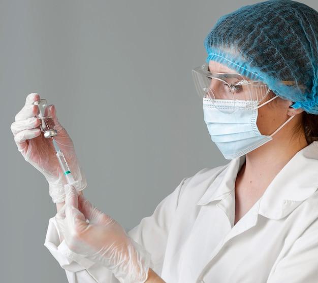 Vista lateral de uma cientista com óculos de segurança e rede para o cabelo segurando uma seringa