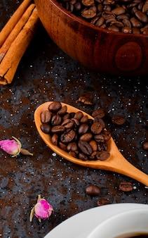 Vista lateral de uma colher de pau com grãos de café sobre fundo preto
