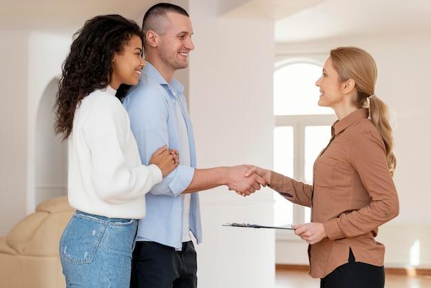 Vista lateral de uma corretora de imóveis apertando as mãos de um casal para um novo contrato