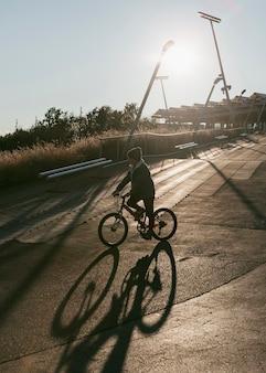 Vista lateral de uma criança andando de bicicleta ao ar livre